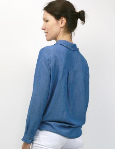 patron de couture Chemise Liseron dans une viscose bleu jean de chez Cousette porté avec un jean blanc, vue 3/4 profil