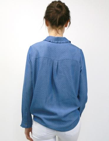 patron de couture Chemise Liseron dans une viscose bleu jean de chez Cousette porté avec un jean blanc, vue de dos