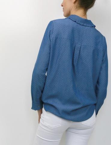 patron de couture Chemise Liseron dans une viscose bleu jean de chez Cousette porté avec un jean blanc, vue 3/4 dos main dans la poche