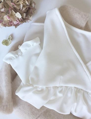 patron de couture Modèle Eugenie version blouse dans un tissu blanc présenté plié sur un pull Des Petits Hauts nude