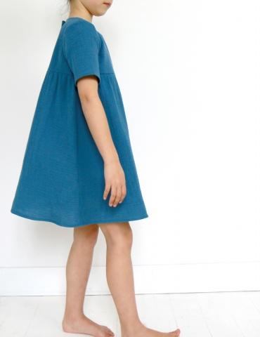 patron de couture Robe Bouton d'or manches courtes réalisée dans une double gaze bleue, vue de profil en pied