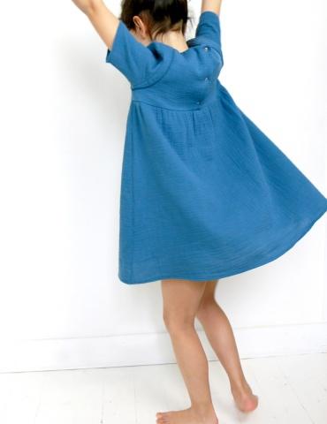 patron de couture Robe Bouton d'or manches courtes réalisée dans une double gaze bleue, vue de dos en train de danser
