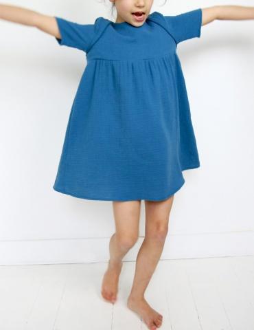 patron de couture Robe Bouton d'or manches courtes réalisée dans une double gaze bleue, vue de face en train de danser