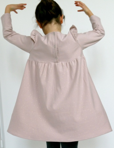 patron de couture Robe Bouton d'or manches longues en sweat Twinkle rose Atelier Brunette, vue de dos en train de danser