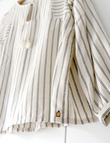 patron de couture Blouse Petites Choses dans une viscose beige rayée, focus sur le bijou de vêtement en bois cousu au bas de la blouse