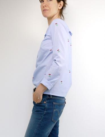 patron de couture Blouse Be Pretty réalisée dans un tissu rayé bleu et blanc avec cerises brodées, vue de 3/4