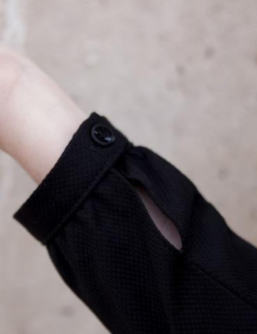patron de couture Robe Be Pretty pour femme enceinte réalisée dans un élégant tissu noir, gros plan sur le poignet