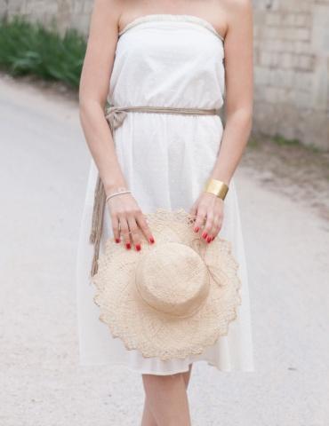 patron de couture Robe bustier Coconut réalisée dans un plumetis blanc de chez Cousette, vue de face 3/4 avec chapeau de paille à la main