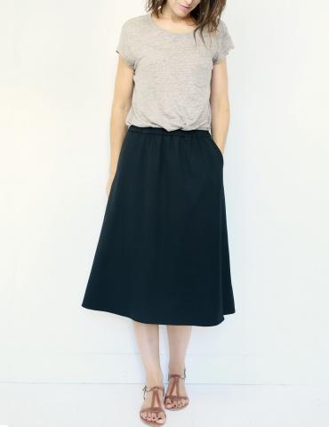 patron de couture Coconut version jupe midi réalisée dans tissu noir, vue de face une main dans la poche