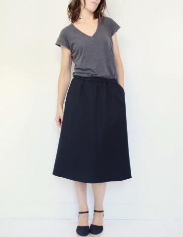 patron de couture Coconut version jupe midi réalisée dans tissu noir, vue de face en pied