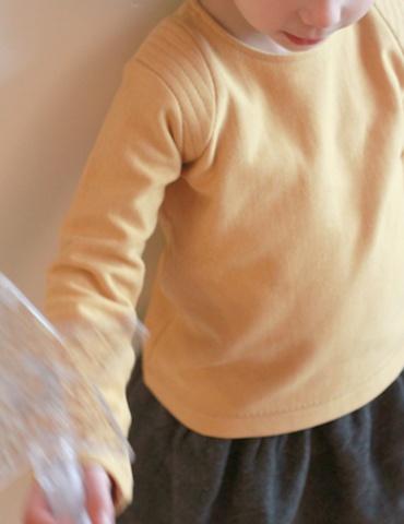 patron de couture Sweat Scammit réalisé dans un molleton moutarde, empiècements épaule dans le même tissu surpiqué, vue de face en contre plongé
