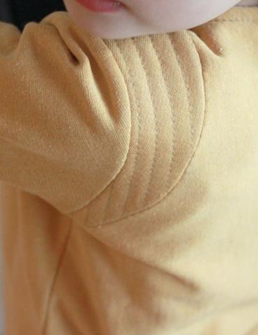 Sweat Scammit réalisé dans un molleton moutarde, empiècements épaule dans le même tissu surpiqué, focus sur l'empiècement épaule
