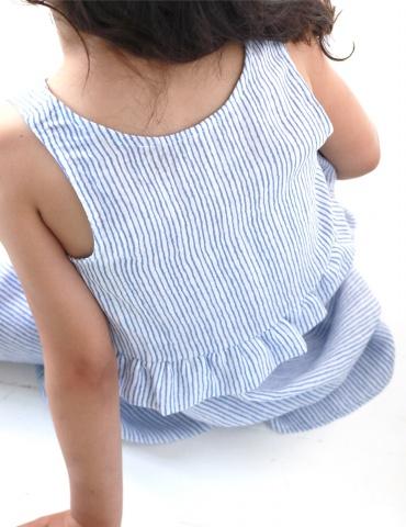patron de couture Robe Petite Lune réalisée dans un tissu léger rayé bleu et blanc, vue de dos assise