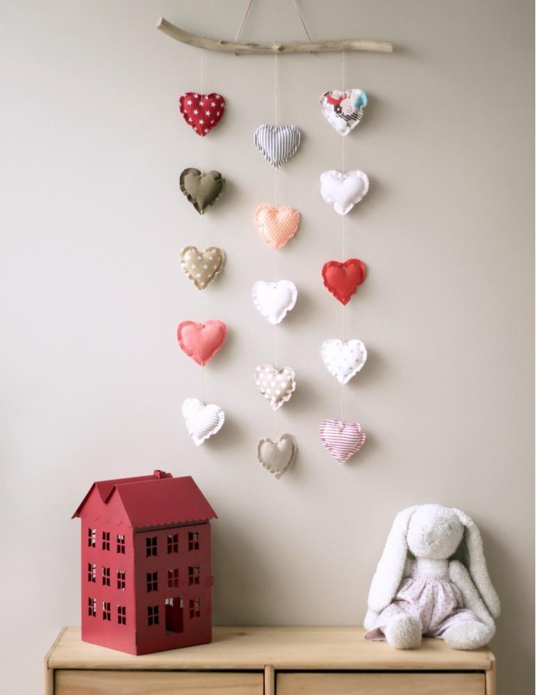 Mobile composé de 15 cœurs dans des tons chauds, accroché au mur