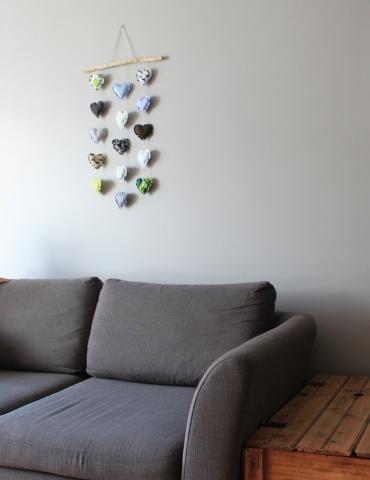 patron de couture Mobile composé de 15 cœurs dans des tons froids, accroché au mur au-dessus d'un canapé gris