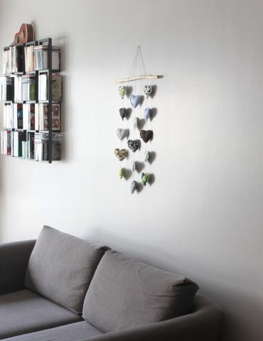 patron de couture Mobile composé de 15 cœurs dans des tons froids, accroché au mur au-dessus d'un canapé gris, vue d'ensemble