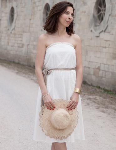 patron de couture Robe bustier Coconut réalisée dans un plumetis blanc de chez Cousette, vue de face en pied avec chapeau de paille à la main