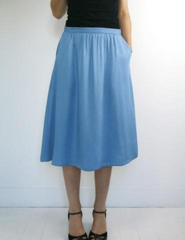 patron de couture Coconut version jupe midi réalisée dans un tencel jean Little Fabrics, vue de face une main dans la poche focus jupe